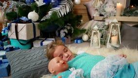 甜睡眠,一点逗人喜爱的女孩睡眠,在火烧的壁炉附近,拥抱玩偶,孩子在a附近睡觉 股票视频
