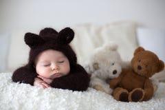 甜矮小的男婴,打扮在手工制造被编织的棕色软的te 免版税库存照片