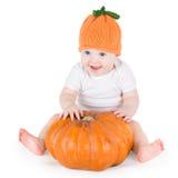 甜笑的女婴用巨大的南瓜 图库摄影