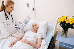 甜精美医生尝试的欢呼她的患者 免版税库存照片