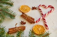 甜糖果锥体的红色心脏用圣诞节香料-肉桂条,茴香星,烘干了在白色背景的桔子 免版税库存图片