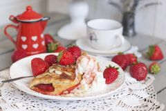 甜自创酥皮点心与草莓装填和冰淇凌的早餐 穿戴女孩褂子早晨白色的咖啡杯 红色水罐用牛奶 送牛奶者 杯子  免版税库存照片