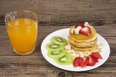 甜草莓薄煎饼和橙汁 免版税库存图片