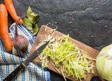 甜菜、红萝卜和圆白菜在烹调期间 在黑暗的背景的构成 图库摄影