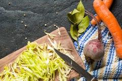 甜菜、红萝卜和圆白菜在烹调期间 在黑暗的背景的构成 免版税库存图片