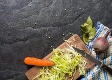 甜菜、红萝卜和圆白菜在烹调期间 在黑暗的背景的构成 库存照片