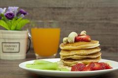 甜薄煎饼用冠上草莓、的腰果和橙汁 库存图片