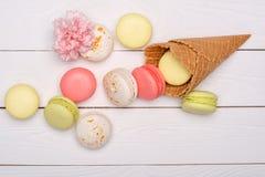 甜蛋白杏仁饼干和称呼与木表面上的花的奶蛋烘饼锥体 甜点背景 图库摄影