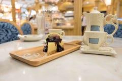甜蛋糕、在桌上把放的茶壶和杯子在咖啡馆 库存图片