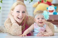 甜说谎在地板上的女孩和她的母亲 免版税库存照片