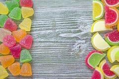 甜鲜美含糖的五颜六色的橘子果酱充满活力的糖果或甜点,顶视图 与拷贝空间的木背景 免版税库存图片