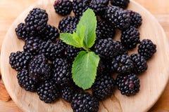 甜黑莓一张顶视图在一块板材的在木背景 未加工和成熟莓果特写镜头用薄菏 库存照片