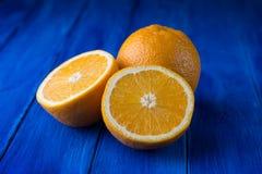 甜整个桔子和两个一半在蓝色木背景 库存图片