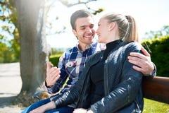 甜年轻夫妇坐长凳在公园 库存照片