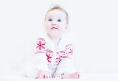 甜婴孩在一个白红色冬天编织了毛线衣 图库摄影