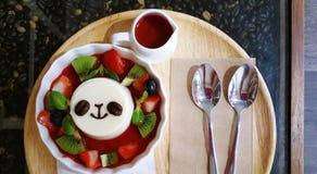 甜水果的糖浆和熊猫面对布丁 免版税库存图片