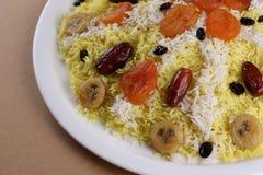 甜plov或肉饭用干果子和被澄清的黄油在大白色板材:东部烹调 关闭 库存图片
