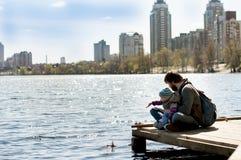 生与一个小儿子投掷的小卵石在河 库存照片