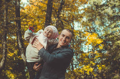 生与一个小孩在秋天公园 免版税库存照片
