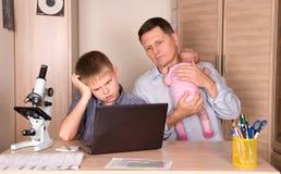 生与一个新出生的婴孩在他的帮助他的有地方教育局的手上儿子 库存照片