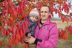 生与他的儿子在秋天,父亲举行他的他的胳膊的儿子在樱桃树附近在秋天 库存图片