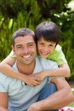生与他的拥抱在庭院里的儿子 免版税图库摄影