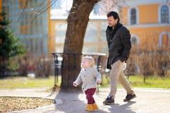 生与使用他的小孩的儿子走和户外 免版税库存图片
