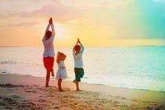 生与做瑜伽的儿子和女儿在日落海滩 免版税图库摄影