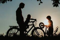 生与儿子和女儿骑马自行车在日落 免版税图库摄影