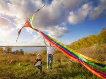 生与儿子在使用与风筝的秋天 库存图片