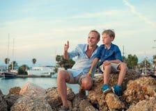 生与儿子在日落时间的热带海港口 库存图片