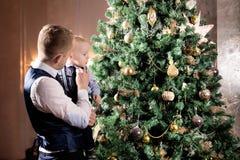 生与儿子,在圣诞树附近的家庭 节假日 免版税库存图片