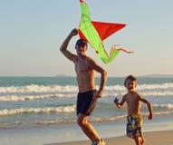 生与儿子,在海岸使用的日落 库存照片