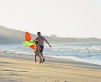 生与儿子,在海岸的日落与风筝,愉快的家庭 库存图片