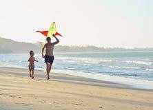 生与儿子,在演奏风筝,愉快的家庭的海岸的日落 免版税库存图片