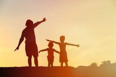 生与儿子,并且女儿剪影使用在日落 免版税库存照片