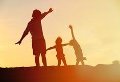生与儿子,并且女儿剪影使用在日落 免版税库存图片