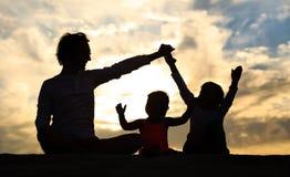 生与儿子,并且女儿剪影使用在日落 库存照片