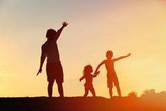 生与儿子,并且女儿剪影使用在日落 库存图片