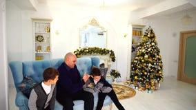 生与儿童游戏体育比赛并且获得乐趣坐蓝色沙发在有圣诞树的欢乐装饰的室 股票视频