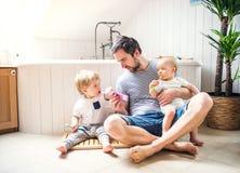 生与在家刷牙的两个小孩在卫生间里 图库摄影