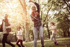 生与女儿低谷举行jum的公园母亲的赛跑 库存图片