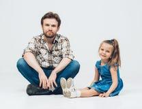 生与女儿坐在牛仔裤的地板 免版税图库摄影