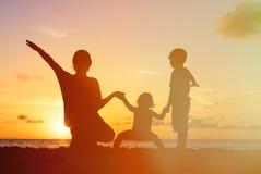 生与孩子剪影获得乐趣在日落 免版税库存图片