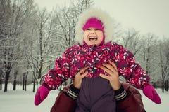 生与小女儿获得乐趣在冬天公园 免版税库存图片