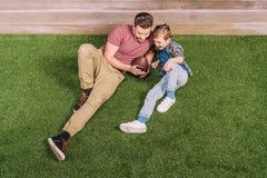 生与放置在草的球和小儿子在后院 免版税库存图片