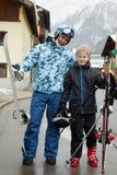 生与有滑雪的雪板和儿子在街道 免版税库存照片
