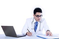 医生与膝上型计算机一起使用 库存照片