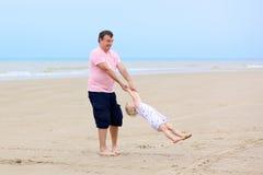 生与获得的女儿在海滩的乐趣 免版税库存照片