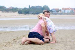 生与获得的女儿在海滩的乐趣 免版税图库摄影